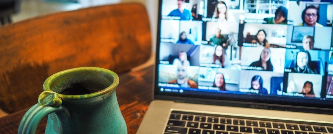 picture of a zoom call at home, a coffee mug next to the laptop