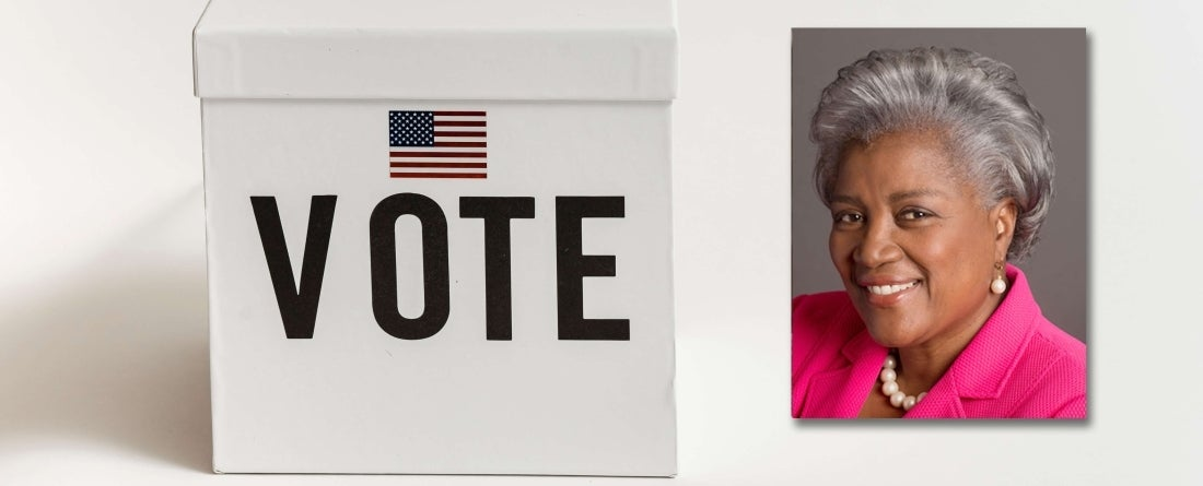 "Donna Brazile headshot over image of box that says ""VOTE"" and voting stickers on table"